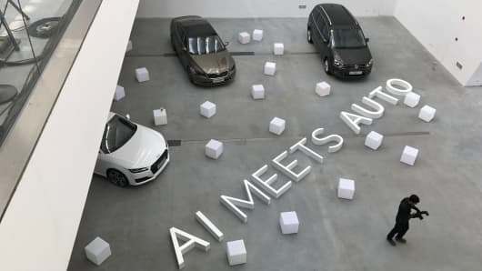 "A staff member walks past a slogan which read ""AI Meets Auto"" at a news conference held by Volkswagen China and Chinese AI company Mobvoi, in Beijing, April 6, 2017."