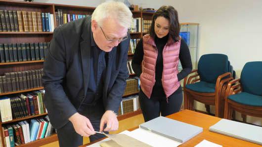 Iceland National Archivist Eirikur Gudmundsson shows Meg Tirrell the 1703 census.