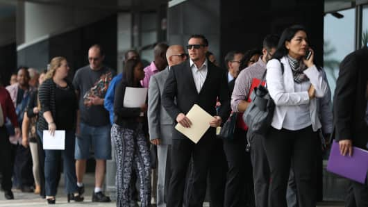 People stand in line as they wait to get into the JobNewsUSA job fair at the BB&T Center in Sunrise, Florida.
