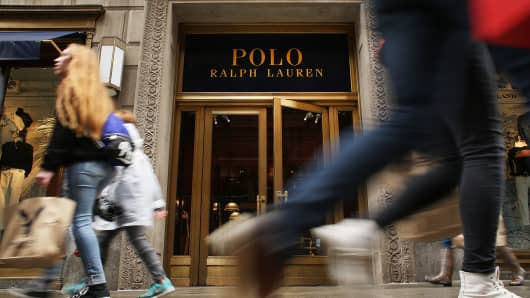 People walk by Ralph Lauren's Fifth Avenue Polo store on April 4, 2017 in New York City. The luxury brand announced on Tuesday that it will close the exclusive location, just doors down from Trump Tower.
