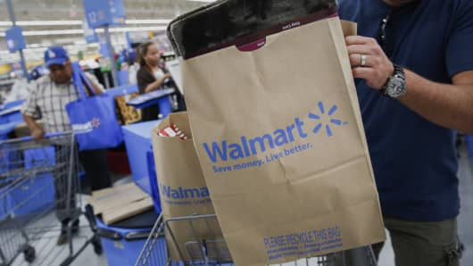 A customer puts a bag of purchases into a shopping cart at a Wal-Mart Stores Inc.
