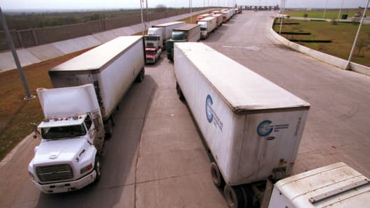 Trucks from Mexico wait to enter the United States at a border crossing point.