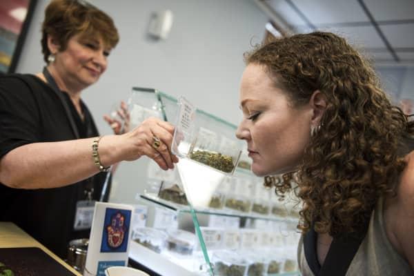 A customer at Takoma Wellness Center in Takoma Park, is shown inventory by Stephanie Kahn, owner of the medical marijuana dispensary.