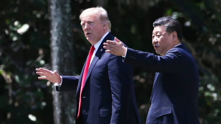 President Donald Trump (L) and China's President Xi Jinping walk along the front patio of the Mar-a-Lago estate after a bilateral meeting in Palm Beach, Florida, April 7, 2017.