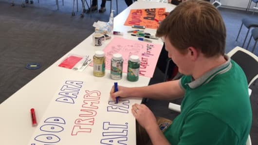 Alnylam staff member Chris Theile works on signs for this weekend's March for Science.