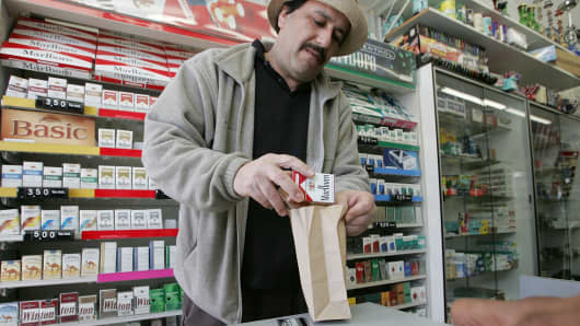 A shop owner sells a pack of cigarettes to a customer in San Francisco.
