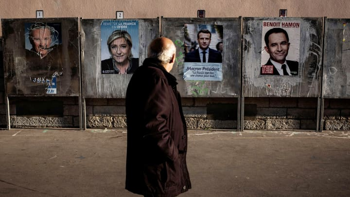 A man passes by campaign posters for the French presidential election, on official billboards on April 21, 2017 in Lyon, ahead of the first round of the French presidential election which will take place on April 23.