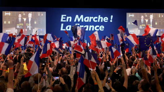 A screen announces the results of the first round of the French Presidential Elections naming Founder and Leader of the political movement 'En Marche !' Emmanuel Macron with 23.7% and National Front Party Leader Marine Le Pen with 22% of the vote at Parc des Expositions Porte de Versailles on April 23, 2017 in Paris, France.