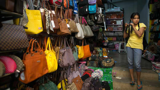 A shop selling counterfeit Chinese made luxury brand ladies bags at an outdoor market in the Golden Triangle, situated along the Thai- Burma border in Tachiliek, Myanmar. Chinese copies boasting well known brands flood this market allowing Thai shoppers and tourists to travel over the border to buy everything from fake iPhones, designer purses, watches and sunglasses.