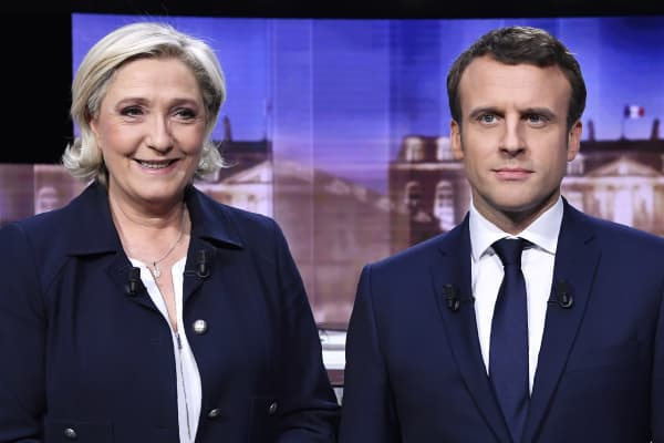 Candidates for the 2017 presidential election, Emmanuel Macron (R), head of the political movement En Marche !, or Onwards !, and Marine Le Pen, of the French National Front (FN) party, pose prior to the start of a live prime-time debate in the studios of French television station France 2, and French private station TF1 in La Plaine-Saint-Denis, near Paris, France, May 3, 2017.