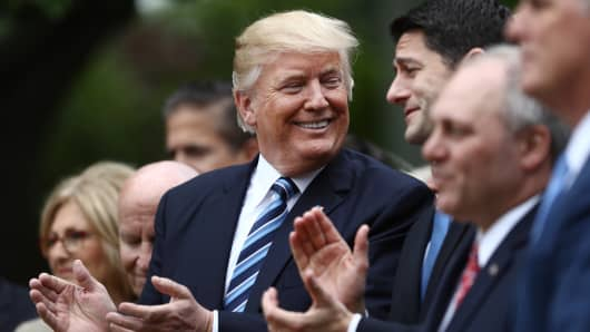 President Donald Trump, center, applauds while standing next to U.S. House Speaker Paul Ryan, a Republican from Wisconsin, during a press conference in the Rose Garden of the White House in Washington, D.C., U.S., on Thursday, May 4, 2017.