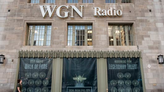 A woman walks past a WGN Radio window display on the side of Tribune Tower in Chicago.