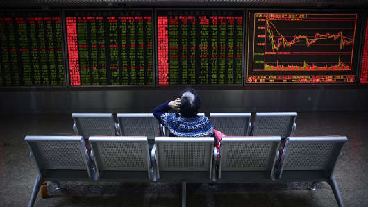 An investor rests on a chair in front of screens showing stock market movements at a securities company in Beijing on November 9, 2016.