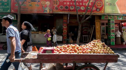 An Uygur man pulls a fruit cart in Urumqi, Xinjiang Uygur Autonomous Region in China.
