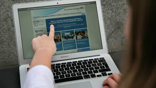 A woman points to the website of the NHS: East and North Hertfordshire notifying users of a problem in its network, in London on May 12, 2017.