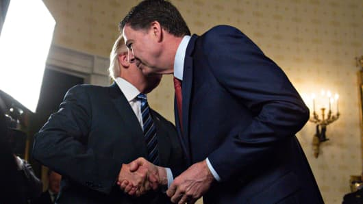 President Donald Trump (L) shakes hands with James Comey, director of the Federal Bureau of Investigation (FBI), during an Inaugural Law Enforcement Officers and First Responders Reception in the Blue Room of the White House on January 22, 2017 in Washington, DC.