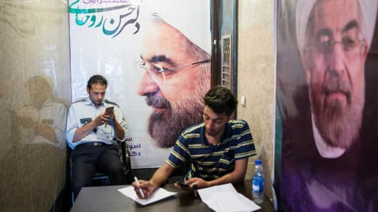 Men use their smartphones to follow election news as posters of Iran's President Hassan Rouhani are seen in Tehran, Iran May 17, 2017.
