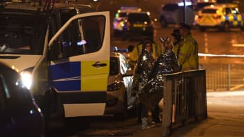 Concert goers wait to be picked up at the scene of a suspected terrorist attack during a pop concert by US star Ariana Grande in Manchester, northwest England on May 23, 2017.