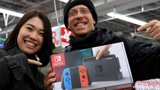 31-year-old Nao Imoto (L) and her husband David Flores, 34 (R) pose with their newly purchased Nintendo Switch game console at a shop in Tokyo on March 3, 2017.