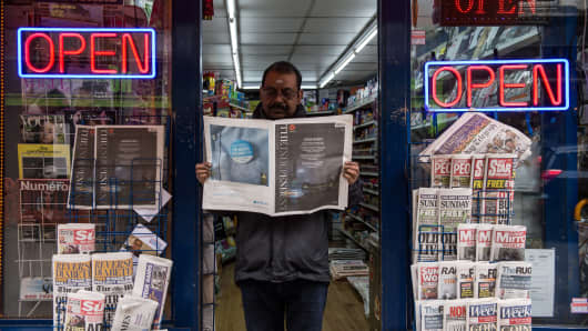 A newsagent reads the last ever print edition of The Independent On Sunday outside his shop in Soho on March 20, 2016 in London, England.