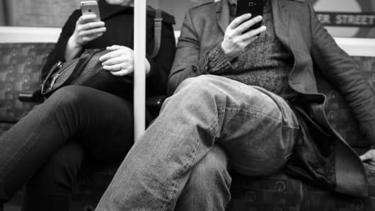 A couple using smartphones on the London Underground.