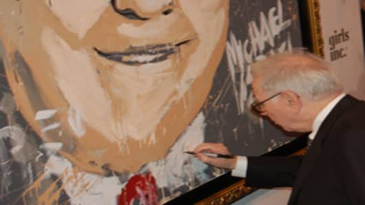 Warren Buffett autographs his portrait.