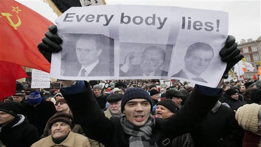 Protester holding a poster depicting Russian Prime Minister Vladimir Putin, Central Election Commission chief Vladimir Churov and Russia's President Dmitry Medvedev shouts slogans during a rally to protest against alleged vote rigging in St.Petersburg, Russia, Sunday, Dec. 18, 2011. About 7,000 demonstrators demanding a rerun of parliamentary elections gathered Saturday in central St.Petersburg for a second weekend of protests against Russia's fraud-tainted vote, a comparatively small crowd that