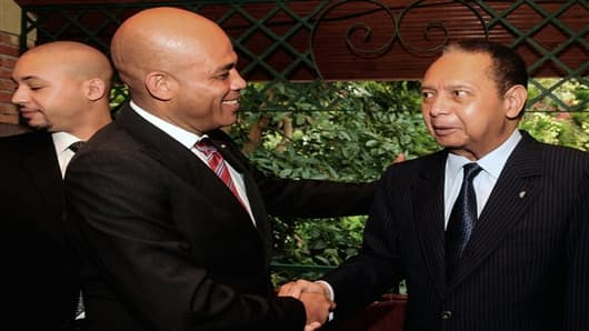 "Haiti's President Michel Martelly, center, shakes hands with former strongman Jean-Claude ""Baby Doc"" Duvalier, right, during a meeting in Port-au-Prince, Haiti. in Oct. 2011."