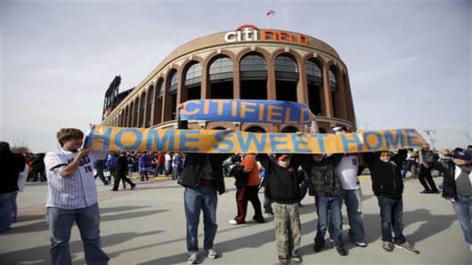 FILE - In this April 13, 2009, file photo, baseball fans hold up a sign in front of the Citi Field before the New York Mets' home-opening baseball game against the San Diego Padres  at Citi Field in New York. A person familiar with the announcement says Major League Baseball will announce Wednesday, May 16, 2012, that the Mets will host the 2013 All-Star game at Citi Field. The person spoke on condition of anonymity on Tuesday, May 15, because MLB did not reveal the purpose of Wednesday's news c