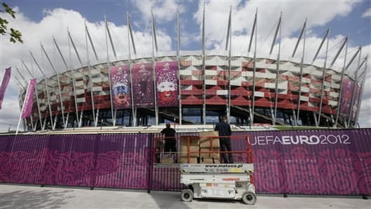 Workers decorate the fence  surrounding Poland's National Stadium in Warsaw, Poland, on Wednesday May 30, 2012. Poland is in full preparation mode as it counts down to the Euro 2012 football tournament that it is co-hosting with Ukraine starting on June 8. (AP Photo/Czarek Sokolowski)