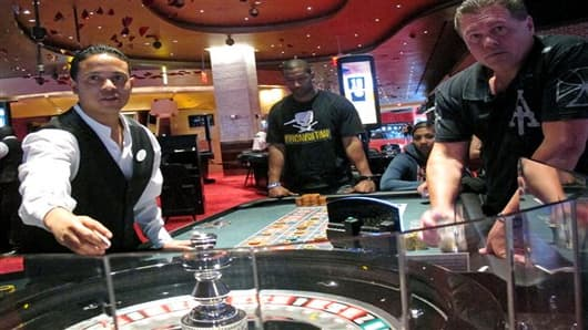 In this May 21, 2012, photo, a dealer at Revel prepares for another round of roulette at the Atlantic City, N.J., casino as patrons await the result. Revel won $14.9 million from gamblers in June, its third month of operation, keeping it mired in eighth place out of Atlantic City's 12 casinos in terms of gambling revenue. (AP Photo/Wayne Parry)