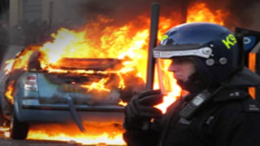 A police officer in riot gear stands near a burning car in Hackney on August 8, 2011 in London, England.