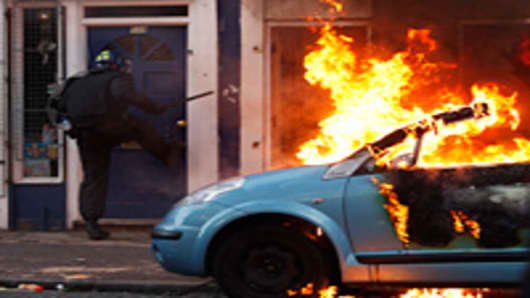 A riot police officer attempts to break down the door of a house next to a burning car as he is targeted by rioters after local residents claimed a baby was still in the property in Clarence Road in Hackney in London, England.