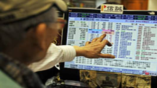 A broker points to a screen showing various share prices at a securities house in Hong Kong on August 9, 2011.