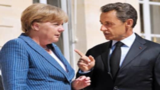 France's President Nicolas Sarkozy (R) welcomes German Chancellor Angela Merkel as she arrives for a meeting on debt crisis.