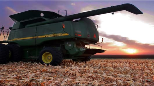 The sun rises while a John Deere combine sitting parked on a freshly harvested corn field with acres of corn left to harvest Saturday, Sept. 9, 2006 near Ashland, Ill. The outlook improved for the nation's corn and soybean crops, which may dampen the effort in Congress to spend billions of dollars in drought aid. (AP Photo/Seth Perlman)