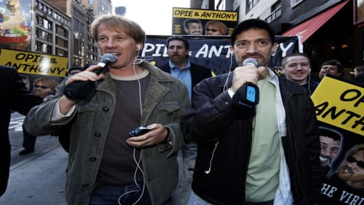 "Radio shock jocks Greg ""Opie"" Hughes, left, and Anthony Cumia, right, greet fans as they leave CBS Radio studios on 57th Street after finishing their first morning show for a one block walk to the XM satellite radio studio while broadcasting live on XM, Wednesday, April 26, 2006, in New York. The ""Opie and Anthony Show"" returned to CBS Radio in seven major markets and will continue to be heard on XM satellite radio. (AP Photo/ Louis Lanzano)"
