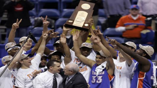 Florida players celebrate with their winning trophy while Florida head coach Billy Donovan (white shirt), foreground left, is congratulated by Laing Kennedy, athletic director of Kent State, following Florida's 75-62 victory over Villanova in  their NCAA Regional final basketball game in Minneapolis, Sunday, March 26, 2006. (AP Photo/Charlie Neibergall)