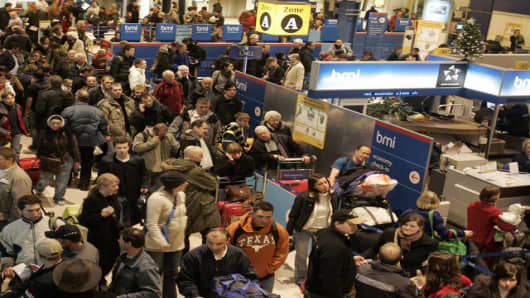 Passengers queue in Terminal one at Heathrow Airport, in London, Thursday Dec. 21, 2006. Several hundred flights from London Heathrow airport were canceled Thursday because of a third day of thick fog. British Airways canceled 180 flights, including all domestic and some European services. (AP Photo/Kirsty Wigglesworth)