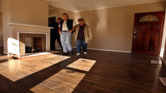 Potential home buyers Shirley, right, and Wayne Minser examine a three-bedroom house as the owner, Carlos Garcia, left, follows Tuesday, Jan. 16, 2007, in the Eagle Rock section of Los Angeles. During December, the median price of homes decreased in Ventura and San Diego counties, but increased in Los Angeles county. (AP Photo/Ric Francis)