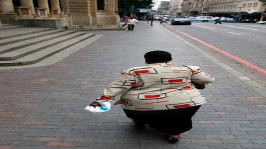 A woman walks on a sidewalk in downtown Johannesburg, Wednesday Nov. 29, 2006. More than one-third of African women and a quarter of African men are estimated to be overweight, and the Word Health Organization predicts that will rise to 41 percent and 30 percent resepctively in the next 10 yaers. (AP Photo/Denis Farrell)