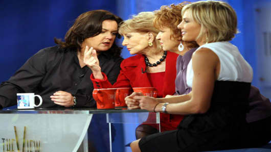 "Rosie O'Donnell, left, talks to co-hosts Barbara Walters, second from left, as Joy Behar, second from right, and Elisabeth Hasselbeck, listen during a commercial break of the taping of the first show of the 10th season of the ABC talk show,"" The View,"" Tuesday, Sept. 5, 2006 in New York. The show began its 10th season with O'Donnell joining the returning Behar, Hasselbeck and Walters. Another change was a cozy, blue-and-orange arena-like set with a glass-top version of the drop-leaf table the la"
