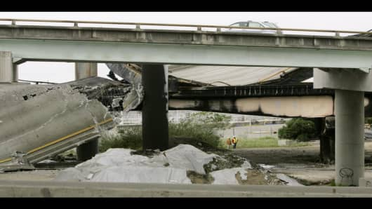 CalTrans workers investigate a crumbled section of freeway ramp which connects Interstate 80 to Interstate 580 in Oakland, Calif., after a tanker carrying gasoline exploded on Sunday, April 29, 2007. In the resulting blaze, a section of freeway that funnels traffic onto the San Francisco-Oakland Bay Bridge collapsed. The truck's driver walked away from the scene and called a taxi, which took him to a nearby hospital with second-degree burns. (AP Photo/Ben Margot)