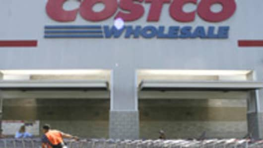 A Costco employee pulls shopping charts at a Costco Wholesale store.