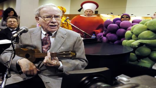 Berkshire Hathaway chairman Warren Buffett plays the ukelele at the Fruit of the Loom stand at the Qwest Center in Omaha, Neb., while touring exhibits prior to the annual Berkshire Hathaway shareholders meeting, Saturday, April 30, 2005. (AP Photo/Nati Harnik)