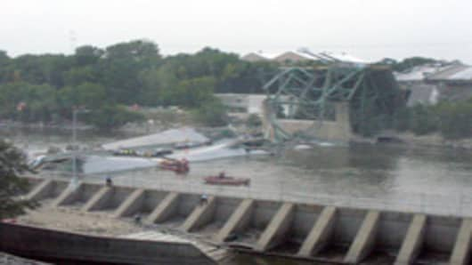 Emergency workers are seen on and near the Interstate 35W bridge in Minneapolis after it collapsed, sending numerous vehicles into the Mississippi River, Wednesday, Aug. 1, 2007. The busy highway bridge that spans the Mississippi River just northeast of Minneapolis collapsed during rush hour Wednesday, sending dozens of cars, tons of concrete and twisted metal crashing into the water. (AP Photo/Jacob Reynolds)