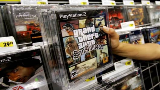 Best Buy store salesman Elia Akau holds up the hot-selling video game, ``Grand Theft Auto: San Andreas,'' for PlayStation, at the store in East Palo Alto, Calif., Wednesday, July 20, 2005. The video game industry on Wednesday changed to adults-only the rating of the game, a best-selling title in which explicit sexual content can be unlocked with an Internet download. The decision followed intense pressure from politicians and media watch groups. (AP Photo/Paul Sakuma)