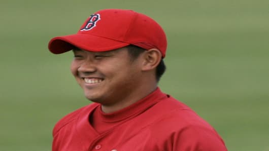 Boston Red Sox pitcher Daisuke Matsuzaka smiles as he runs during a practice prior to a spring training baseball game in Fort Myers, FL, Monday March 12, 2007. Fans flock for his autograph. Cameras record his simplest moves. He's just one of hundreds of rookies at baseball spring training camps this year, but he's swooned over like a rock star. (AP Photo/Charles Krupa)