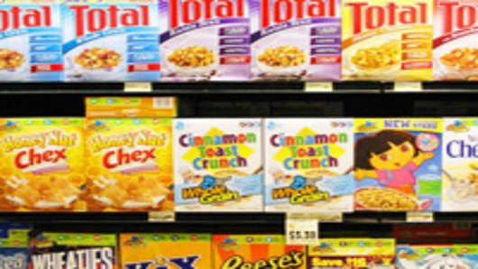 A range of General Mills products line a grocery shelf.
