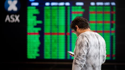 A man uses his mobile phone in front of electronic stock boards at the Australian Securities Exchange (ASX Ltd.) headquarters in Sydney, Australia.